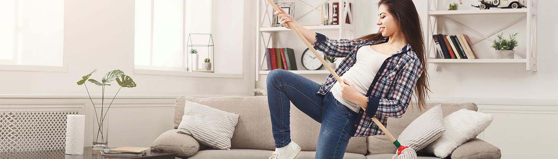 Frau hält Wischmop wie Gitarre - Frühjahrsputz