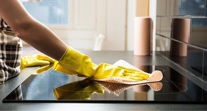 Hände mit Handschuhen putzen den Herd - Frühjahrsputz in der Wohnung