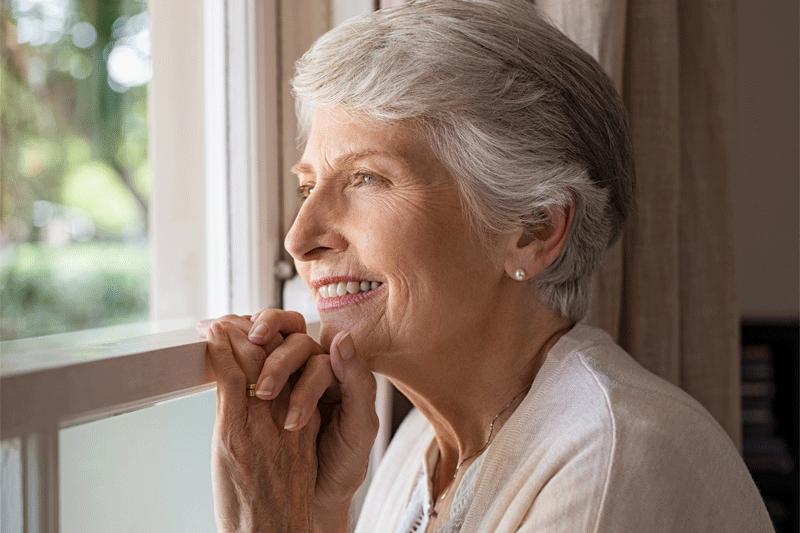 Ältere Frau schaut aus dem Fenster