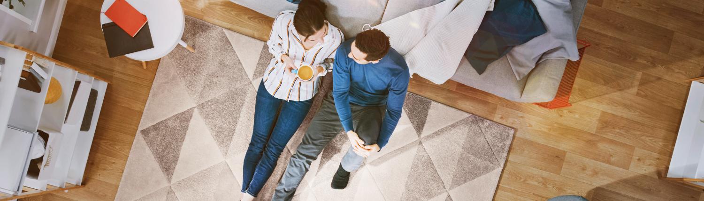 Mann und Frau unterhalten sich gemütlich sitzend auf dem Teppich